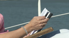Mature woman reading book on a boat Stock Footage