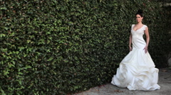 Woman by hedge wearing white wedding dress Stock Footage