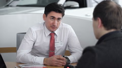 The manager conducts a dialogue with the customer in the car shop Stock Footage