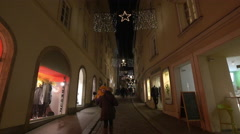 People walking on a street, passing by Rundholz store on Christmas in Graz Stock Footage