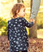 Toddler girl holding hands with her mother on a fall day Stock Photos