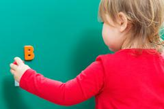 Toddler girl learning her ABCs on a chalkboard Stock Photos