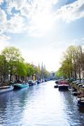 Sunny view of Amsterdam on the river and boats - stock photo