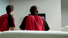 Two young men wearing football shirts watching football on television Arkistovideo