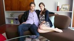 Mid adult couple sitting on sofa, portrait - stock footage
