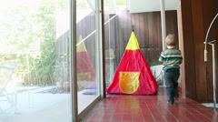 Young boy running into teepee to collect toy dinosaur Stock Footage