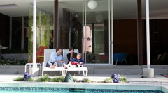 Mother, father and son on sun loungers on patio Stock Footage