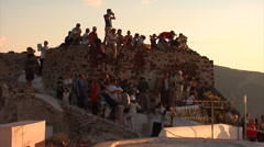 Crowd of tourists watching sunset from the fort in Oia, Santorini, Greece. Stock Footage