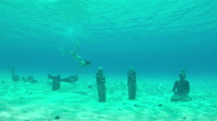 Woman diving underwater exploring sunken statues on the sea bottom Stock Footage