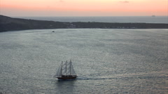 Zoom out from a vintage sailing ship on the Santorini caldera after sunset. Stock Footage
