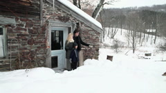 Couple outside rustic house playing with dog Stock Footage