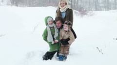 Father carrying son and daughter in snow Stock Footage