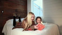 Mother and daughter lying on bed reading book Stock Footage
