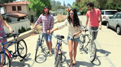 Friends pushing bicycles down a road on vacation Stock Footage