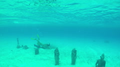 Female diver swimming and snorkeling underwater, discovering sunken statues Stock Footage