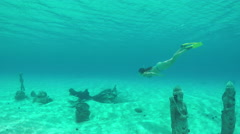 Female diver snorkeling underwater exploring sunken religious statue sanctuary - stock footage