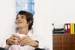 Businessman sitting next to mineral water - stock photo