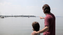 Father and son looking across sea to harbor Stock Footage