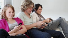 Teenage girl texting on smartphone, friends playing video game - stock footage