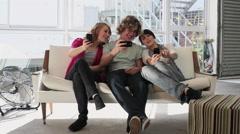 Three teenage friends looking at smartphones - stock footage