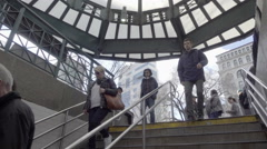People walking down stairs Union Square subway station entrance winter day NYC Stock Footage
