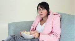 Teenage girl watching TV and eating popcorn Stock Footage