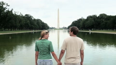 Rear view of young couple by washington monument Stock Footage