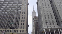 Tilting down Empire State Building to Park Ave intersection cars driving NYC Stock Footage