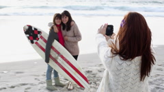 Girl taking photograph of two friends on beach with surfboard Stock Footage