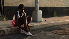 Runner tying shoelaces on sidewalk Stock Footage