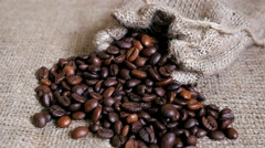 Coffee beans spilled from pouch on sackcloth. Dolly shot. Stock Footage