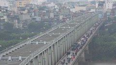 Motorbikes and cars cross a bridge during the busy rush hour in Hanoi, Vietnam - stock footage