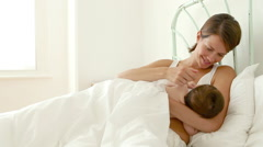 Mother and baby breast feeding in bed Stock Footage