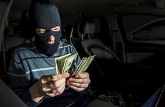 Hacker with a laptop inside a car - stock photo
