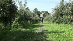Young woman walking in apple orchard Stock Footage