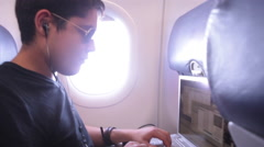 Young Man working on laptop in airplane next to window seat - stock footage