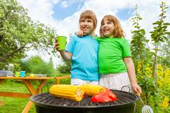 Close-up of sisters grilling corn with paprika Stock Photos