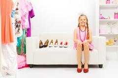 Girl with braids sits on sofa choosing high heels - stock photo