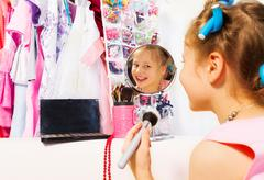 Happy girl makes up with brush looking in mirror - stock photo