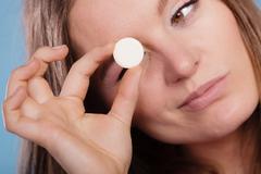 Woman with painkiller pill tablet. Health care. Stock Photos