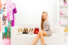 Cute girl sits on sofa choosing high heels shoes - stock photo