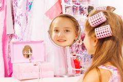 Beautiful small girl reflecting in round mirror - stock photo