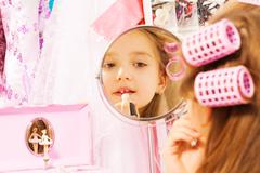 Cute girl making up her face looking in mirror - stock photo