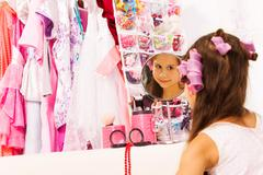 Beautiful girl with hair-curlers looks in mirror - stock photo