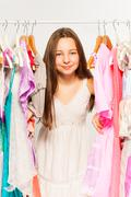 Beautiful girl stands among hangers with clothes Stock Photos