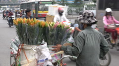 Asia street scene flower vendor bicycle transport busy road Hanoi Vietnam Stock Footage