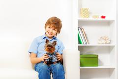Brown Yorkshire Terrier with happy boy sitting - stock photo