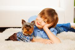 Yorkshire Terrier in pullover with boy on carpet - stock photo