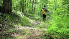 Male cyclist carrying bike through forest Stock Footage