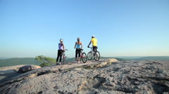 Stock Video Footage of Three cyclists on rocks, scenic view